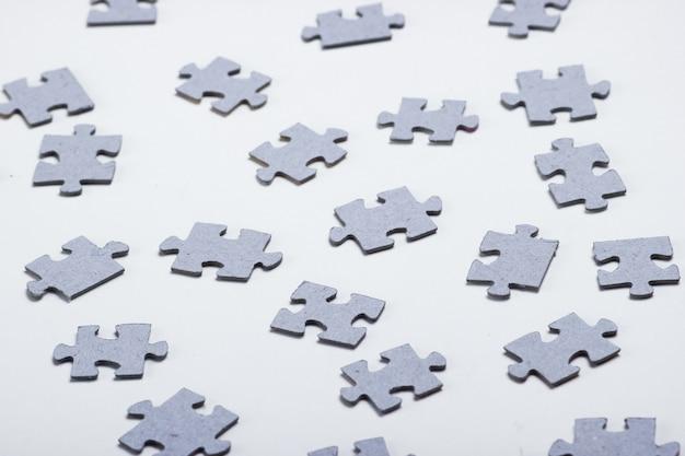 Peças cinza do quebra-cabeça isoladas no branco