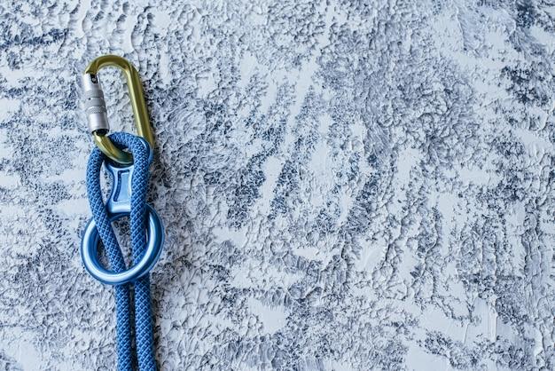 Peças conectadas. equipamento de escalada isolado. parte do mosquetão deitado na superfície de cor branca e cinza.
