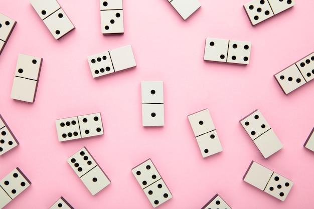 Peças de dominó na superfície rosa