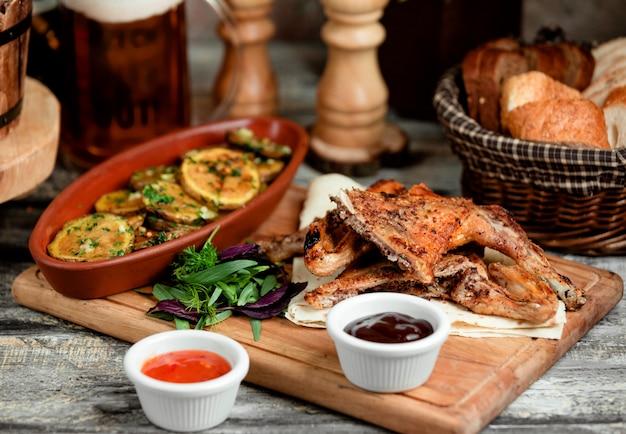 Peças de frango grelhado servidas com fatias de batata assadas e molhos