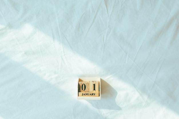 Peças de madeira com o texto 01 de janeiro em folha branca no conceito de ano novo.