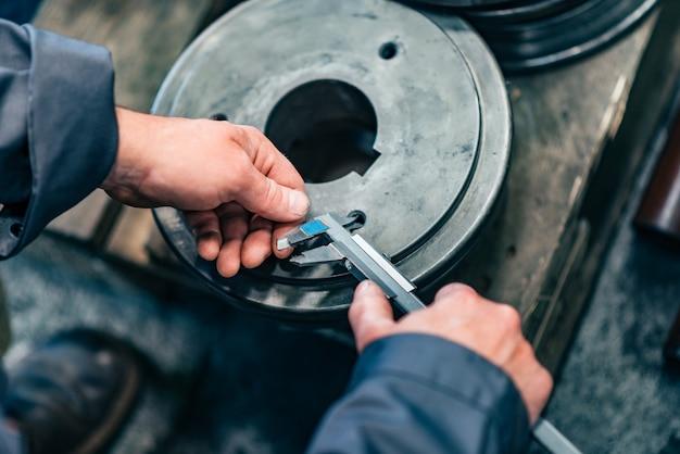 Peças de metal de medição com compasso de calibre vernier, close-up.