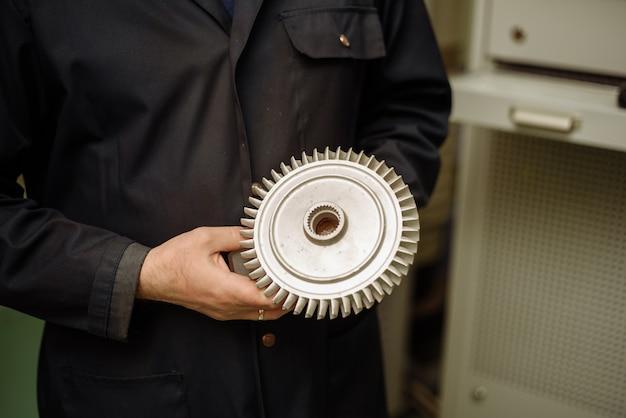 Peças de metal nas mãos de um engenheiro.