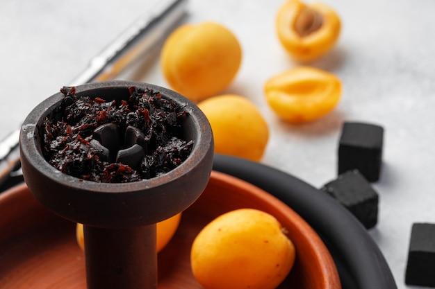 Peças de narguilé com damascos frescos na mesa