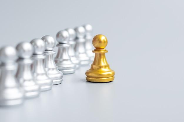Peças de peão de xadrez dourado ou empresário líder destacam-se da multidão de homens de prata. conceito de liderança, negócios, equipe, trabalho em equipe e gestão de recursos humanos