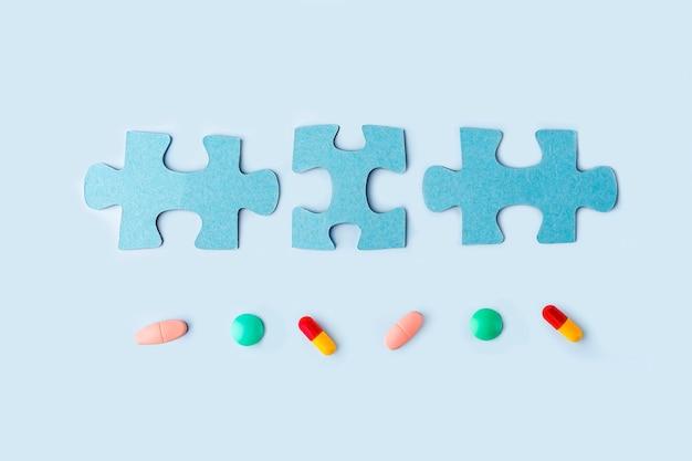 Peças de quebra-cabeça azul com diferentes pílulas e medicamentos. conceito de tratamento de doenças neurológicas: autismo, alzheimer, dimensão. copie o espaço para o texto. dia da conscientização. apoio e aceitação.