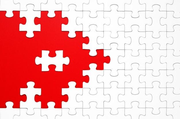 Peças de quebra-cabeça branca sobre um fundo vermelho separados