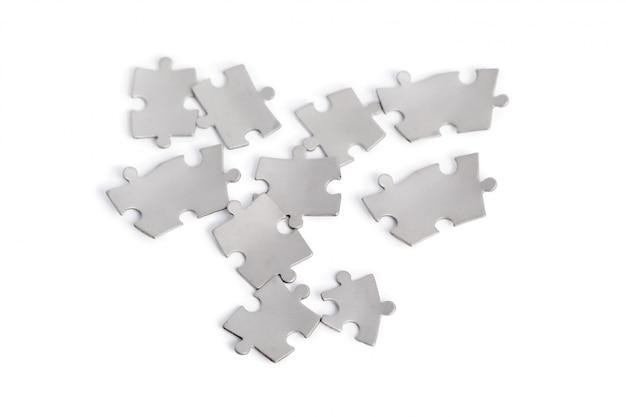 Peças de quebra-cabeça de metal isoladas no branco