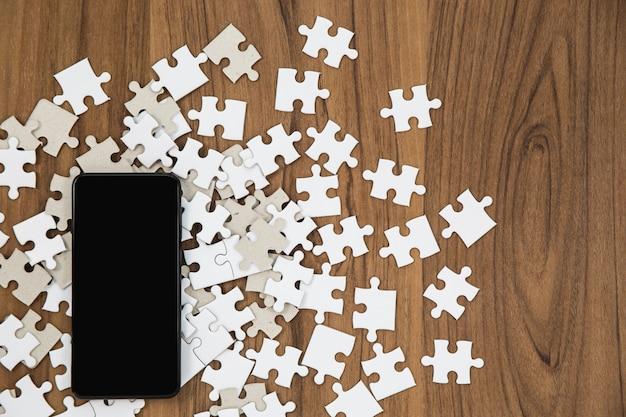 Peças de quebra-cabeça e smartphone na mesa de madeira
