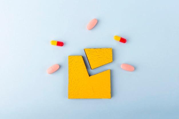 Peças de quebra-cabeça verdes com diferentes pílulas e medicamentos. conceito de tratamento de doenças neurológicas: autismo, alzheimer, dimensão. copie o espaço para o texto. dia de conscientização de apoio e aceitação