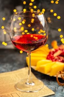 Peças de queijo em vidro de vinho de vista frontal em uma placa de madeira nas luzes escuras de natal