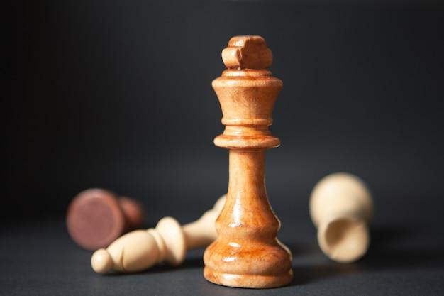 Peças de xadrez de madeira em fundo preto