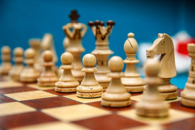 Peças de xadrez de madeira no tabuleiro, brancas antes do início do jogo