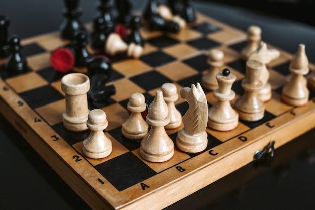 Peças de xadrez de madeira velhas no tabuleiro de xadrez durante o processo de jogo
