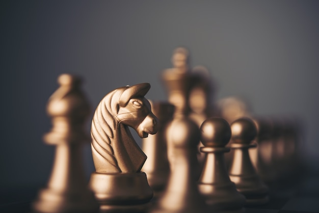 Peças de xadrez de ouro em um tabuleiro de xadrez.