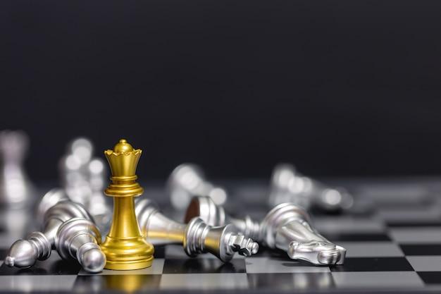 Peças de xadrez de ouro vencem a equipe de xadrez de prata sobre fundo preto