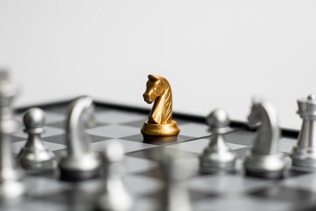 Peças de xadrez de um ouro que ficam contra o conjunto completo de peças de xadrez em fundo branco.