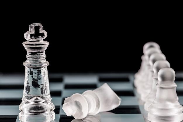 Peças de xadrez de vidro em um tabuleiro de xadrez de vidro com reflexão, sobre um fundo preto.