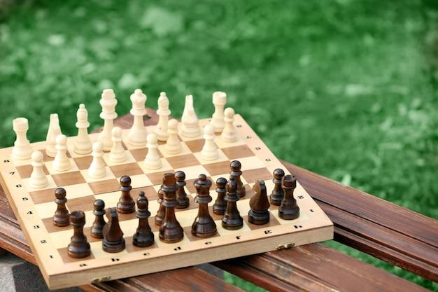Peças de xadrez e tabuleiro de jogo no fundo da natureza