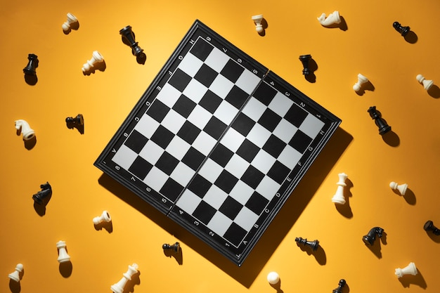 Peças de xadrez e tabuleiro de xadrez em fundo amarelo