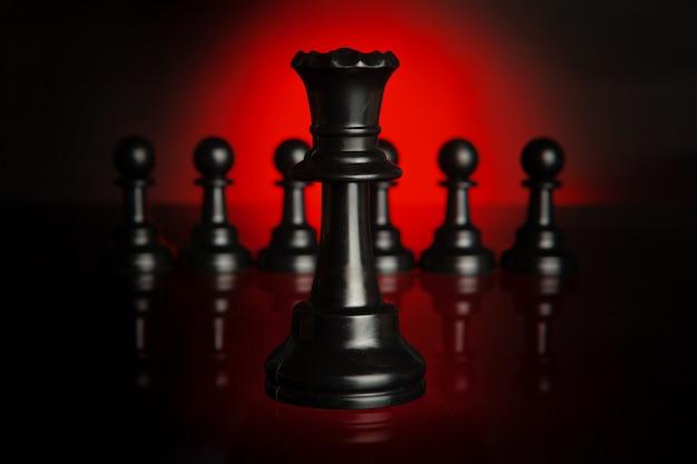 Peças de xadrez em fundo escuro com luz de fundo vermelha close-up