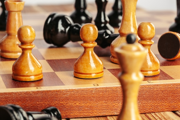 Peças de xadrez em um tabuleiro de xadrez de madeira contra um fundo escuro