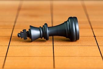 Peças de xadrez em um tabuleiro de xadrez de madeira