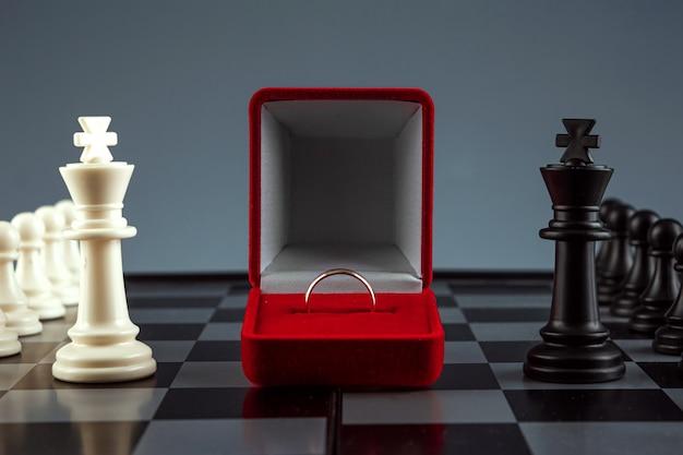Peças de xadrez em um tabuleiro de xadrez e uma caixa com um anel de ouro