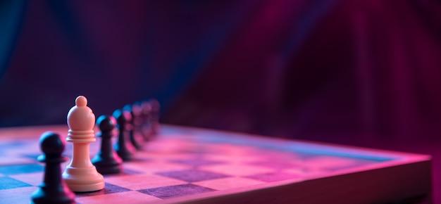 Peças de xadrez em um tabuleiro de xadrez em um fundo escuro filmadas em cores rosa-azul neon. a figura de um xadrez.