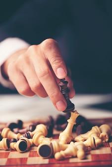 Peças de xadrez no tabuleiro. fundo de madeira preto atrás.