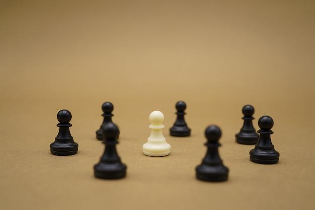 Peças de xadrez pretas e um peão branco na superfície marrom