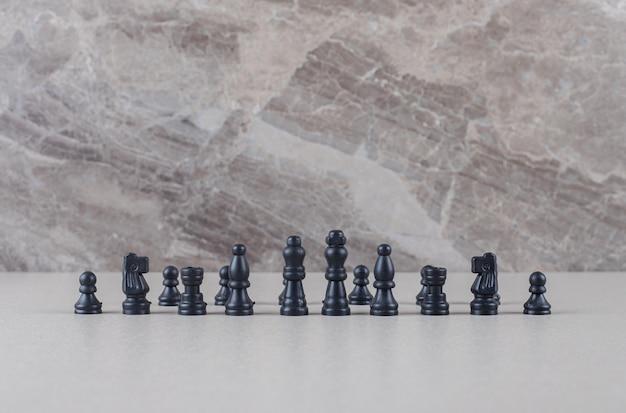 Peças de xadrez pretas exibidas em mármore