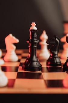 Peças de xadrez sobre a mesa com imagem vertical do conceito de negócios e motivação de foco seletivo
