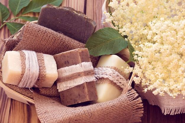 Peças decoradas de vários sabonetes secos em uma cesta com ancião branco