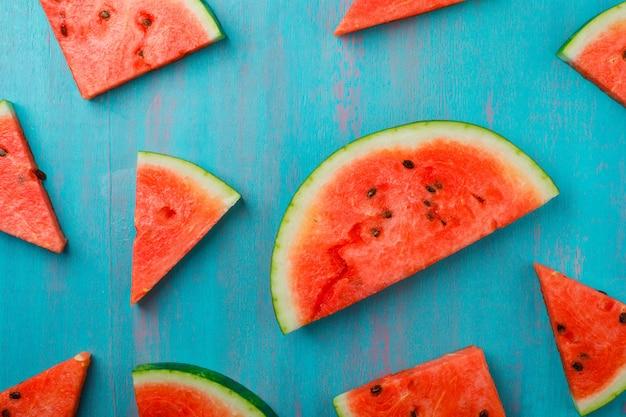 Peças dispersas da melancia no fundo azul, vista superior.