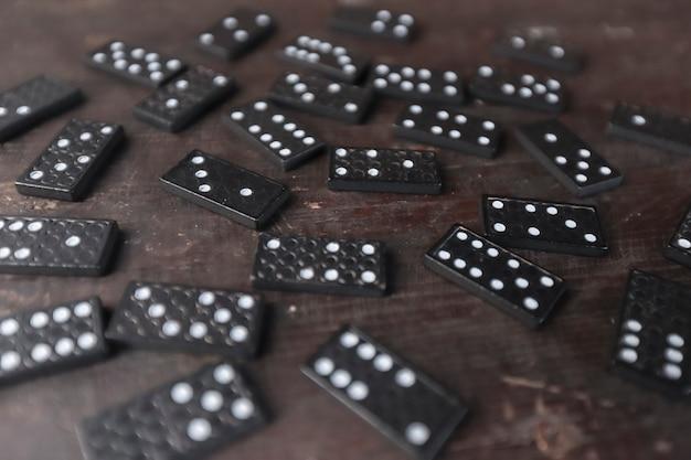Peças do jogo de dominó espalhadas na velha mesa de madeira, foco seletivo e perspectiva