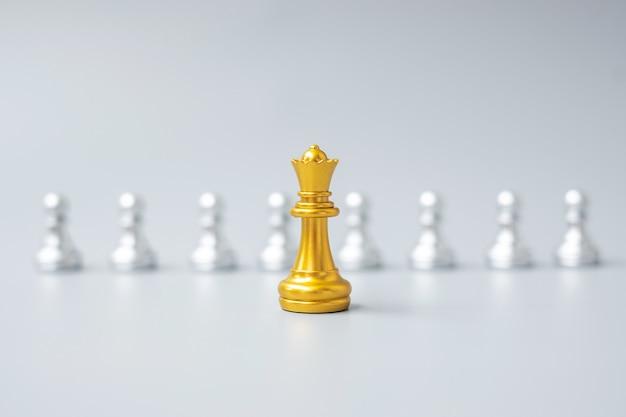 Peças do rei xadrez dourado ou empresário líder destacam-se da multidão de homens de prata. conceito de liderança, negócios, equipe, trabalho em equipe e gestão de recursos humanos