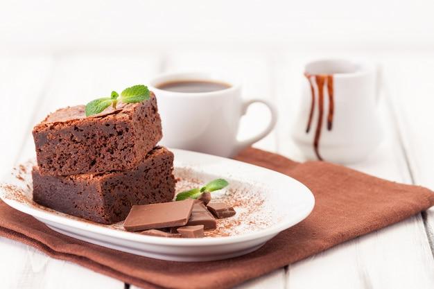 Peças quadradas de brownie de chocolate em pilha no prato branco decorado com folhas de hortelã e cacau em pó