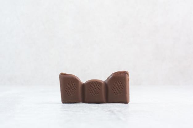 Pedaço de barra de chocolate com fundo de pedra. foto de alta qualidade