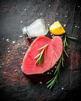Pedaço de bife de atum cru com especiarias, alecrim e limão. em rústico escuro