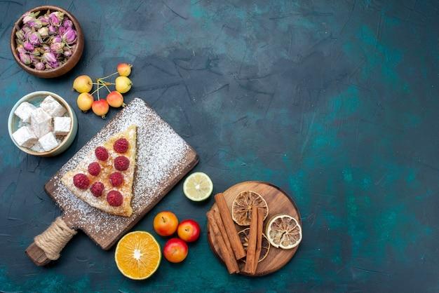 Pedaço de bolo assado de cima com framboesa e canela em uma mesa azul escuro com baga e açúcar torta assar biscoito