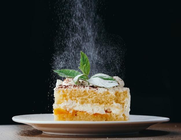 Pedaço de bolo biscuit com creme branco decorado com hortelã e açúcar energizado.