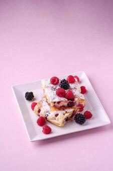 Pedaço de bolo caseiro, duas fatias de torta com bagas de framboesa e amora, açúcar em pó, em um prato quadrado branco na rosa