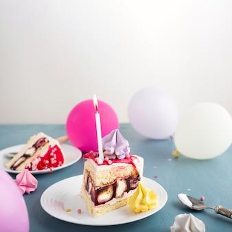 Pedaço de bolo com balões coloridos