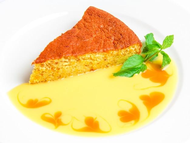 Pedaço de bolo com molho amarelo