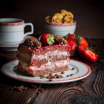 Pedaço de bolo com morango e migalhas e xícara de chá no prato