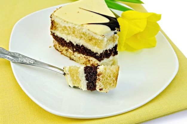 Pedaço de bolo com um garfo e tulipas amarelas em um prato branco e um guardanapo amarelo isolado no fundo branco