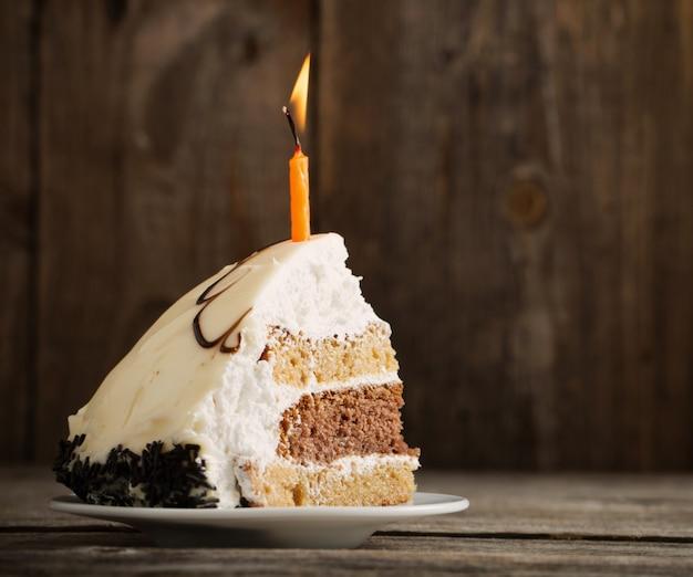 Pedaço de bolo de aniversário em fundo de madeira