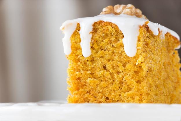 Pedaço de bolo de cenoura caseiro com nozes e creme de confeiteiro.
