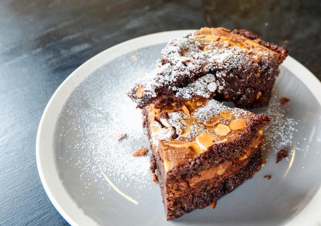 Pedaço de bolo de chocolate cacau com nozes e açúcar de confeiteiro